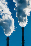 Two chimneys with dramatic clouds of smoke. Stock Photos