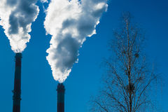 Two chimneys with dramatic clouds of smoke. Stock Photography