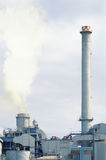 Two chimneys in a factory emitting smoke damaging the environment. Stock Photo
