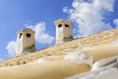 Two chimneys on a tiled roof Stock Image