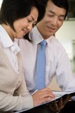 Two Chinese businesspeople reading a document Stock Images