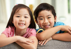 Two  Chinese Children Relaxing On Sofa At Home Royalty Free Stock Image