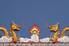 Two Chinese Dragon sculptures on the roof in the blue sky background Stock Image