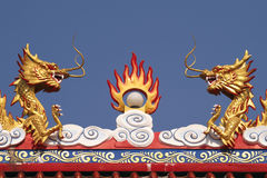 Two Chinese Dragon sculptures on the roof of a temple in Thailand Royalty Free Stock Photos