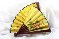 Two Chinese fan on a silk background. Royalty Free Stock Image