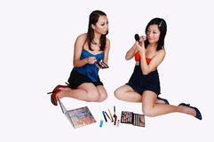 Two Chinese girls doing makeup. Royalty Free Stock Photo
