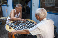 Two Chinese man playing Chinese Chess Xiangqi in a street of the city of Dunhuang, China Royalty Free Stock Photo