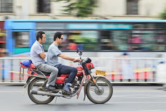 Two Chinese men on a motorcycle. XIANG YANG-CHINA-JULY 1, 2012. Two men on gas motorcycle on July 1, 2012 in Xiang Yang. Demand for gas motorcycles in China Royalty Free Stock Photos