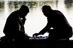 Two Chinese old man play Chinese chess. At lakeside Royalty Free Stock Photos