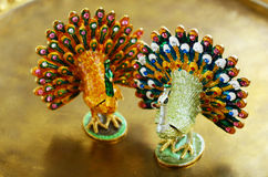 Two chinese peacock statuette on golden background Stock Photography