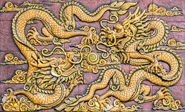 Two Chinese style golden dragons. Two Chinese style golden dragons fighting as low relief technique mass product artwork Royalty Free Stock Images