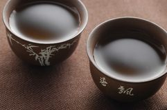 Two chinese tea cups. On wooden table with tea Stock Photography