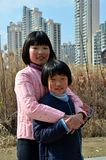Two Chinese teen sisters hug Shanghai China. Shanghai, China - February 16, 2013: Two teen girls stand and hug in a rural area in Shanghai, China. Shanghai's royalty free stock photo