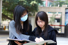 Two Chinese university students on campus. They are discussing homework and presentations on campus, working very hard. They look very smart but one of them is Royalty Free Stock Photo