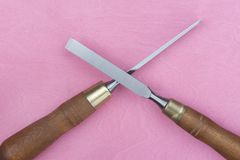 Two chisels on a pink background. Two professional chisels on a pink wood background. Visible wood grain Stock Images