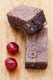Two chocolate brownies with two glace cherries. On a wooden board Stock Photos