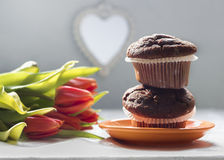 Two chocolate chip muffins and tulips Royalty Free Stock Photos