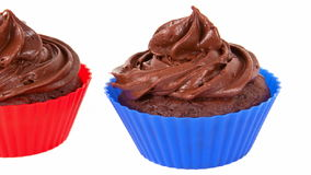Two Chocolate Cupcakes. In red and blue holders stock video