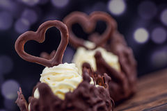 Two chocolate desserts filled with white cream on wooden table, dessert with chocolate hearts for valentines or wedding day Stock Photo