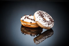 Two chocolate donuts lying over dark backgroung. Two fresh sweet chocolate donuts lying over dark backgroung Royalty Free Stock Photos