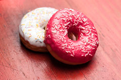 Two chocolate donuts lying on wooden background Stock Photos