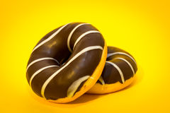 Two chocolate donuts on the yellow background.  stock photography