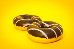 Two chocolate donuts on the yellow background.  stock images