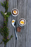 Two chocolate Easter eggs, spoon with yolk and shell. Two chocolate Easter eggs next to spoon with yolk and chocolate shell on the wood background with flowers Stock Photography