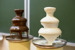 Two chocolate fountains. Two chocolate white and dark fondue fountains on school party Stock Image