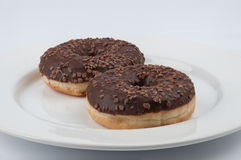 Two chocolate glazed rin donuts served on a white plate Royalty Free Stock Photography