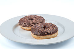 Two chocolate glazed ring donuts on white plate Royalty Free Stock Images