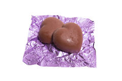Two chocolate heart candy in puple foil on white background.  Royalty Free Stock Photos