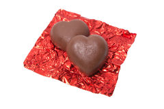 Two chocolate heart candy in red foil on white background Royalty Free Stock Photo