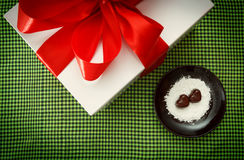 Two chocolate heart-shaped candies on a brown plate next to gift box with red ribbon against green checked fabric background. Top view Royalty Free Stock Image