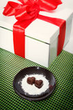 Two chocolate heart-shaped candies on a brown plate next to gift box with red ribbon against green checked fabric background. Top view Stock Photos