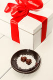 Two chocolate heart-shaped candies on a brown plate next to gift box with red ribbon against wooden background Royalty Free Stock Images