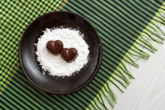 Two chocolate heart-shaped candies on a brown plate with sugar powder against green checked fabric background Royalty Free Stock Image