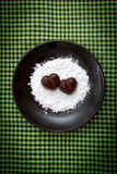 Two chocolate heart-shaped candies on a brown plate with sugar powder against green checked fabric background Royalty Free Stock Photos