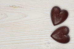 Two chocolate hearts on light wood background Royalty Free Stock Photo