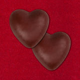 Two chocolate hearts on red Royalty Free Stock Photo