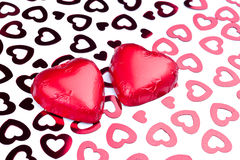 Two chocolate hearts wrapped in red foil Royalty Free Stock Photography