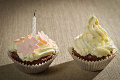 Two chocolate muffin with candle. And vanilla cream Stock Photos