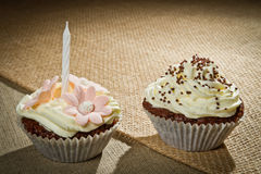 Two chocolate muffin with candle and vanilla cream. On brown canvas Stock Photo