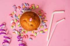 two chocolate muffins, a birthday candle. Party for girls. Caps and tinsel and multi-colored sweets on a pink background. stock photography