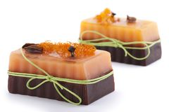 Two chocolate orange soaps with clove, Illicium, cinnamon and loofah on top  on white background Royalty Free Stock Images
