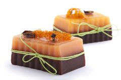 Two chocolate orange soaps with clove, Illicium, cinnamon and loofah on top  on white background Stock Photography