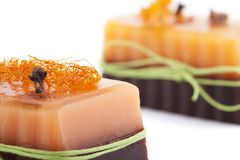 Two chocolate orange soaps with clove, Illicium, cinnamon and loofah on top  on white background Stock Image