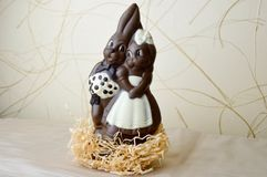 Two chocolate rabbits. Two tasty, embracing, chocolate hares, a loving couple. On a light beige background Stock Photography