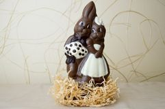 Two chocolate rabbits. Two tasty, embracing, chocolate hares, a loving couple. On a light beige background Stock Photos