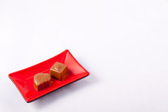 Two Chocolates on a Square Plate. Two chocolates presented on a red square plate set on a white background with copy area Royalty Free Stock Photo